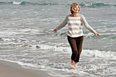 Caucasian woman wading on beach