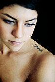 Hispanic woman with strong tattoo on shoulder