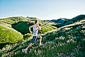 Caucasian athlete running on rural hills