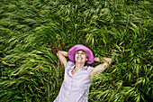 Caucasian woman laying in tall grass
