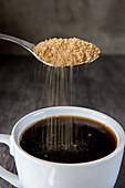 Brown Sugar Being Poured into Cup of Coffee