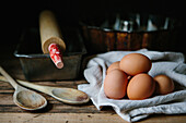 Brown Eggs with Wood Spoon, Baking Tins and Roller