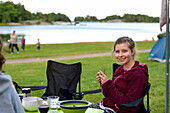 Girl knitting outside, camping ground, Vaestervik, Smaland, Sweden