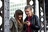Girls listening to music outside in Speicherstadt, Hamburg, Germany, Europe