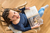 Girl sat reading on a rocking chair in living room, Hamburg, Germany, Europe