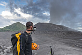 "Eruption of the active Tavurvur volcano and ash cloud. Man with gas mask and helmet in the front, the green cone of the ""Vulcan'' volcano in the background, New Guinea, New Britain, South Pacific"