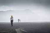 Expeditionsteilnehmer laufen durch die giftigen Gase der Vulkane Marum und Benbow mit Helm und Gasmaske, Vanuatu, Insel Ambrym, Süd Pazifik