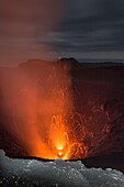 High lava explosion of the active volcano Yasur with lava bombs and toxic gases. The crater in the foreground is brightened with a flashlight. Overcast, dark sky at the blue hour, Vanuatu, Tanna Island, South Pacific