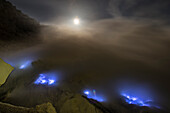 Burning sulfur with blue flames of the volcano Ijen at night with full moon and stars, East Java, Ijen volcano, Indonesia