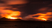 Views of the volcanoes Marum and Benbow at a distance at night. Lava illuminating the gases and the night sky is coloured as red as blood, Vanuatu, Ambrym Island, South Pacific
