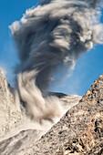Langzeitbelichtung einer großen Asche-Eruption und Gesteinsauswurf an der offenen Flanke des Vulkans Batu Tara in der Flores Sea bei Tage vor blauem Himmel mit Vulkan-Gasen und Asche, Insel Komba, Flores Sea, Indonesien