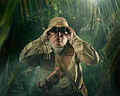 Caucasian hunter peering through binoculars in jungle