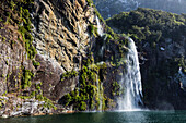 Waterfall over sheer cliffs to remote river, Te Anau, Southland, New Zealand