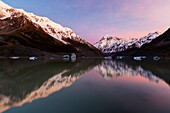 Snowcapped mountains reflecting in still lake, Mount Cook Village, Mckenzie Country, New Zealand