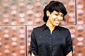 Hispanic woman smiling near metal wall