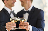 Caucasian gay grooms toasting with champagne at wedding