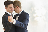 Caucasian gay grooms dancing at wedding