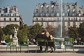 Caucasian couple admiring fountain in urban park, Paris, Ile-de-France, France