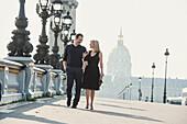 Caucasian couple walking on urban bridge