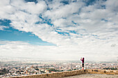 Caucasian woman photographing scenic view of cityscape, Granada, Spain