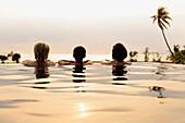 Women admiring scenic view in infinity pool