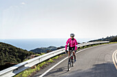 Caucasian woman biking on remote mountain road