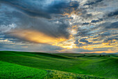 Dramatic sky over rolling hills in rural landscape