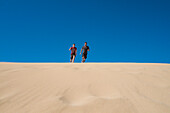 Caucasian father and son running on sand dune