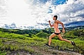 Mixed race athlete running on rural hilltop