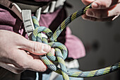 Athlete tying knot on climbing harness