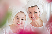 Caucasian mother and daughter wearing towels in hair