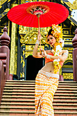 Asian woman with parasol on stairs of ornate Buddhist temple, Chiang Mai, Chiang Mai, Thailand