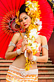 Asian woman with flower headdress holding parasol