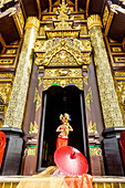 Asian woman standing in ornate temple doorway, Chiang Mai, Chiang Mai, Thailand
