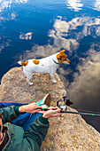 Caucasian man fishing with dog in remote lake
