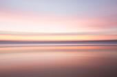 Defocused view of ocean waves on beach under sunset sky