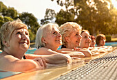 Older Caucasian women leaning on edge of swimming pool