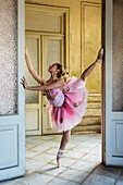 Hispanic ballet dancer posing in dilapidated mansion