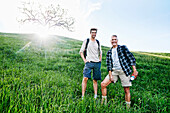 Caucasian father and son standing on grassy hillside