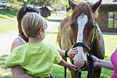 Caucasian mother and son petting horse in paddock