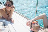 Caucasian couple sunbathing on boat deck