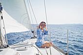 Caucasian woman using binoculars on boat deck