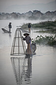 Asian fishermen fishing in canoes on river
