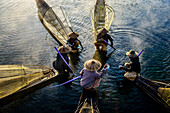 High angle view of Asian fishermen fishing in canoes on river