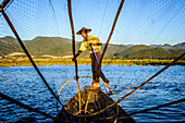 Asian fisherman using fishing net in canoes on river