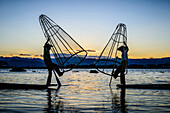 Asian fishermen using fishing nets in canoe on river