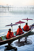 Asian monks under parasols in canoe on river