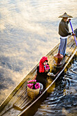 Asian farmer and daughter rowing in canoe on river