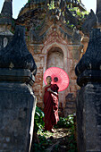 Asian monk-in-training with parasol walking on Buddhist shrine