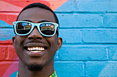 Close up of Black man wearing colorful sunglasses